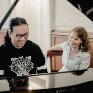 Piano teacher and student laughing